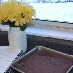chocolate cake in square pan next to painted mason jar with flowers