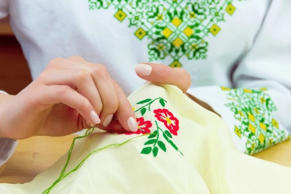 woman hand embroidering flowers