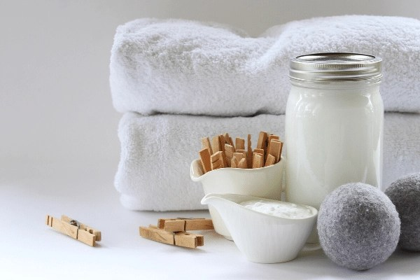 homemade laundry soap in mason jar with two wool dryer balls, wooden clothes pegs and white towels