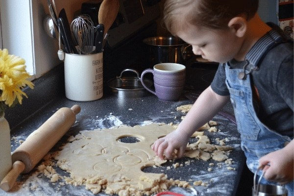 child cutting shortbread cookies with cookie cutter