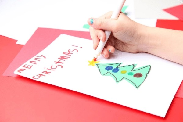 child colouring a handmade Christmas card