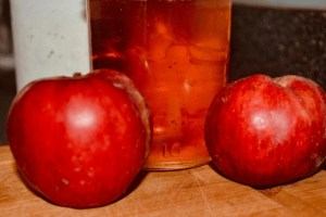 apple jelly in jar beside apples