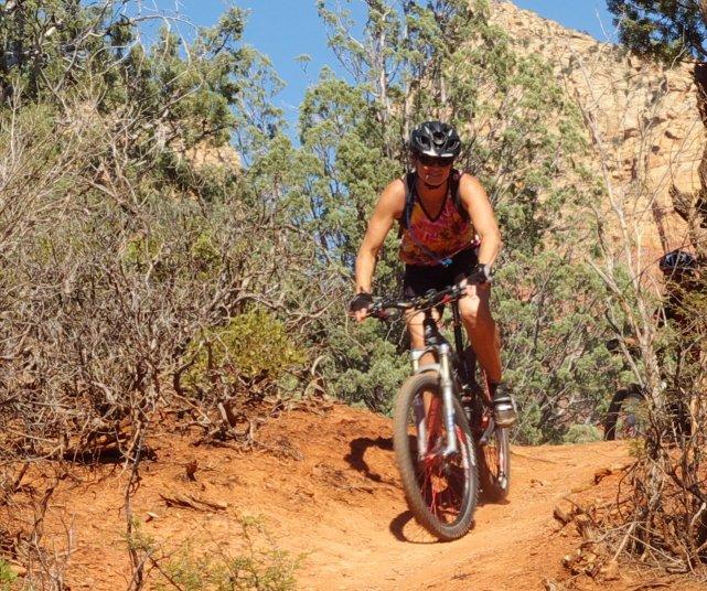 A mountain biker crests a hill.