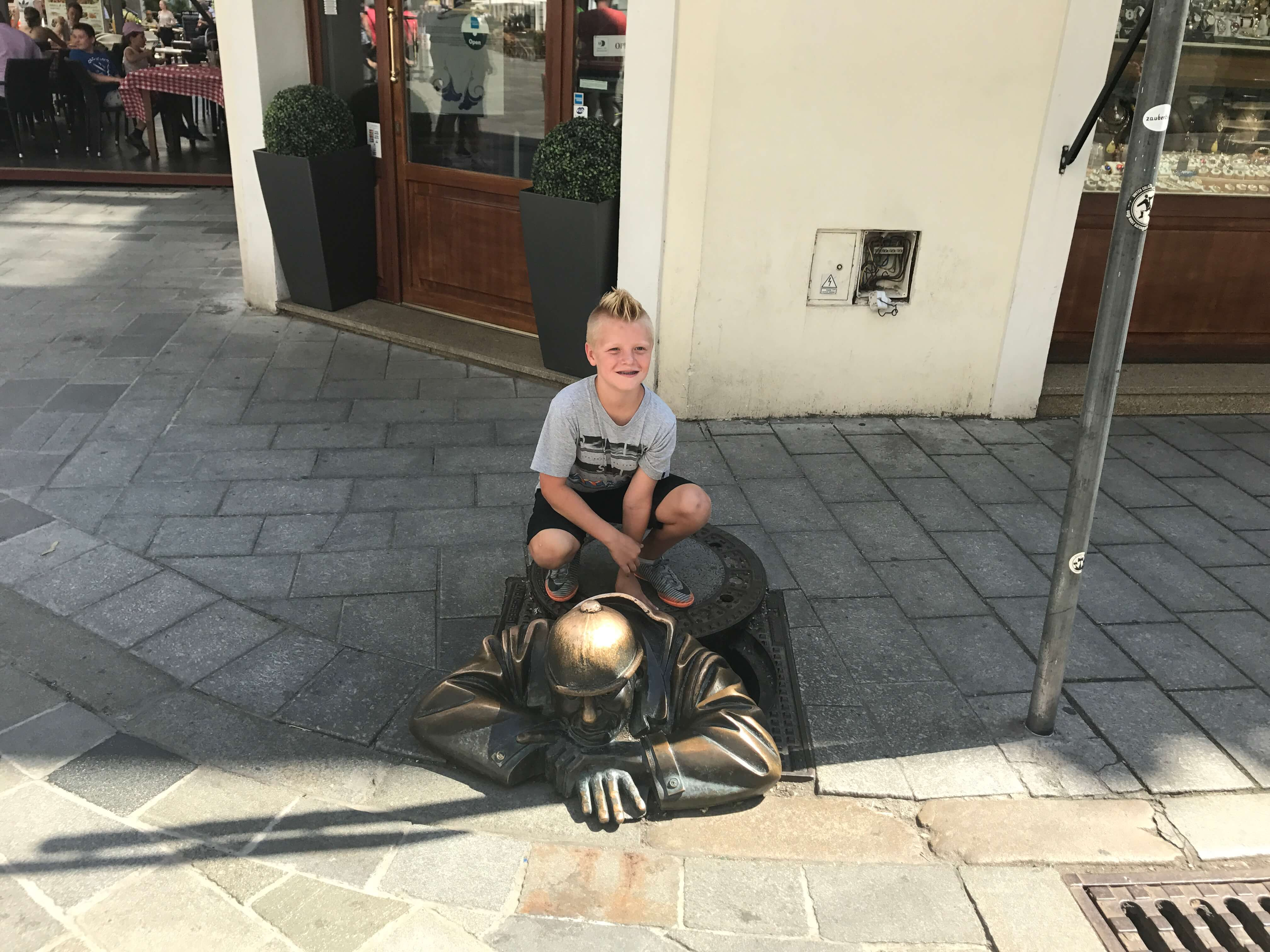 Aiden posing with Cumil the Man at Work statue.