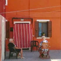 Two elderly residents enjoy the shade and the slight breeze on Burano in late July 2020. (photo by Melissa Paul.)