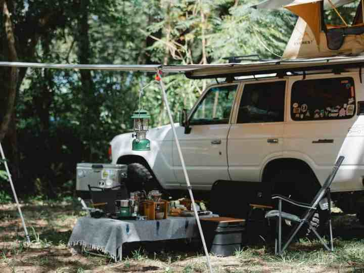 offroader with awning and tent on roof placed in green forest