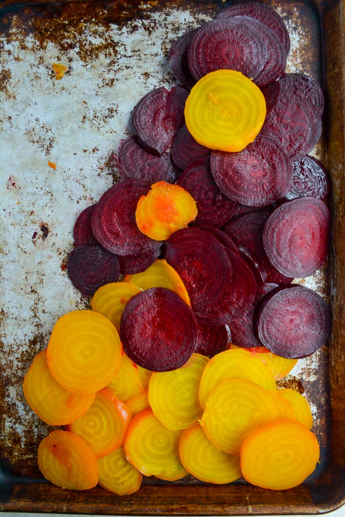 Roasted golden beets and red beets sliced on a baking tray ready for Roasted Beet Salad with Citrus & Walnut Feta Gremolata