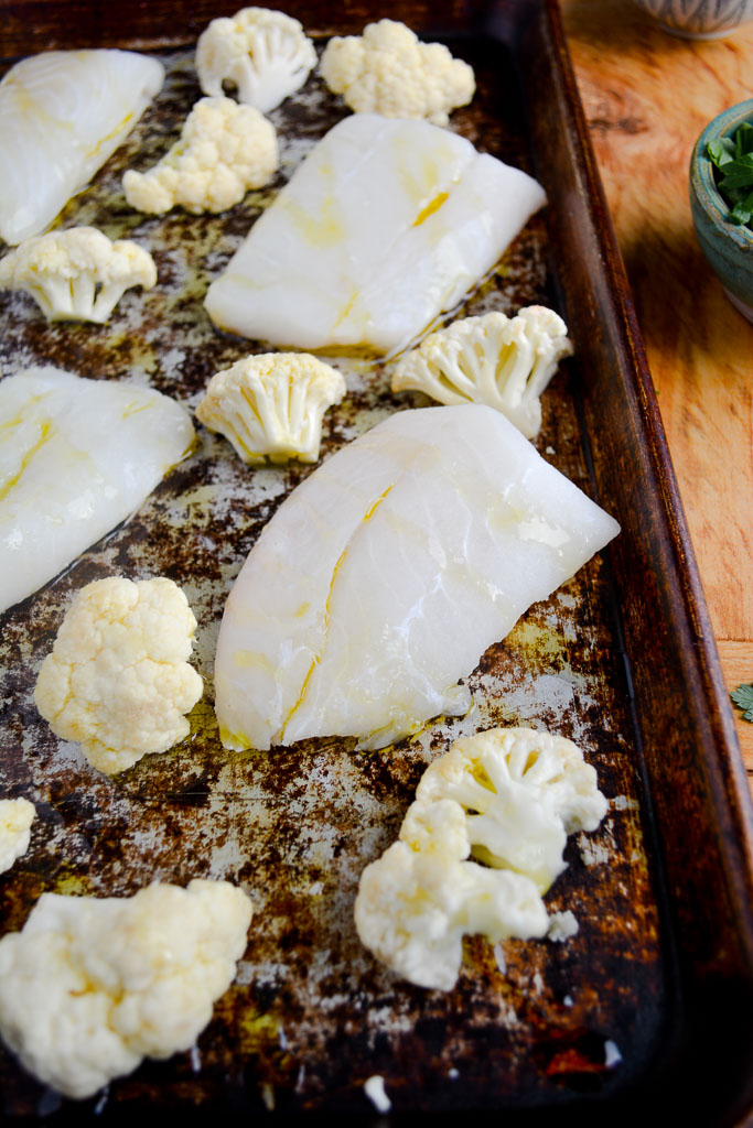 Cod filets and cauliflower florets on a baking sheet drizzled with olive oil
