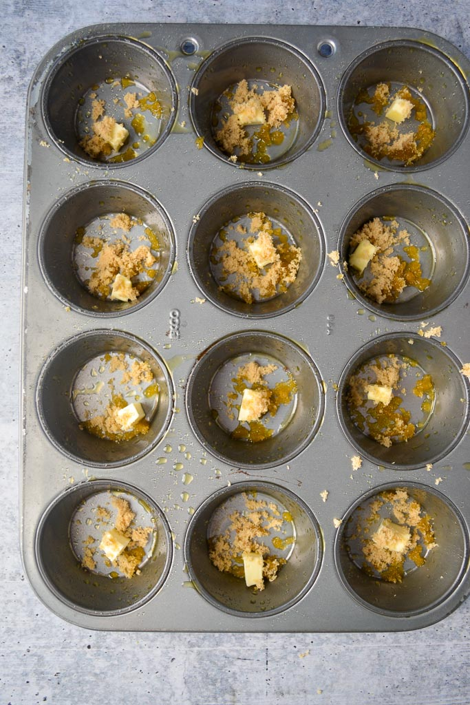 Greased muffin tin with butter and brown sugar