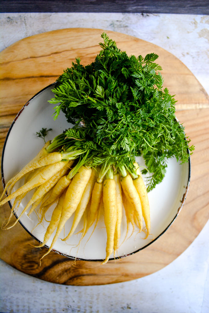 White baby carrots with bright green carrot tops