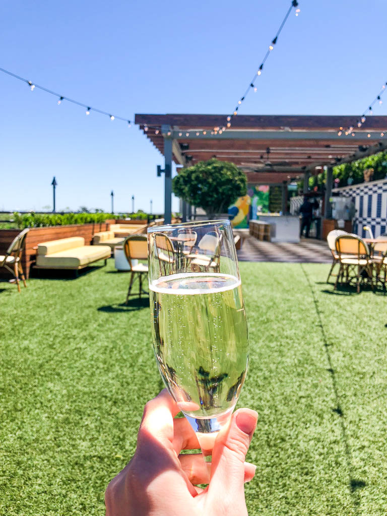 Glass of champagne on the colorful rooftop bar Peregrin at the top of the Perry Lane Hotel in Savannah, Georgia