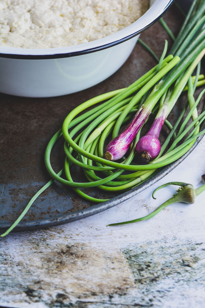 Spring onions and garlic scapes with proofed focaccia dough