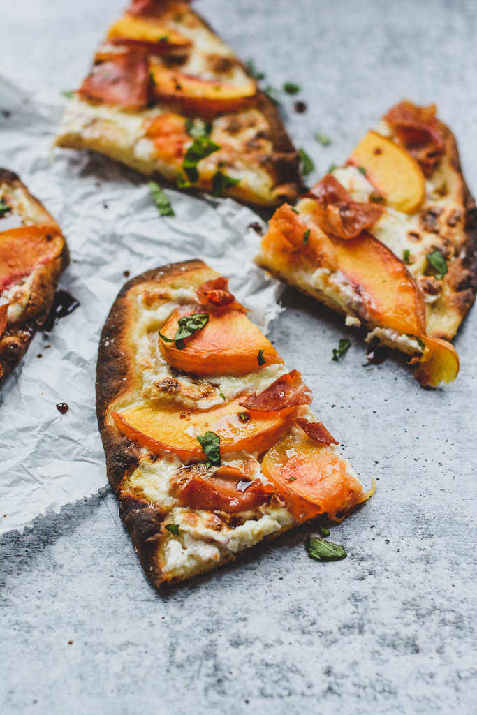 Slices of peach and prosciutto pizza