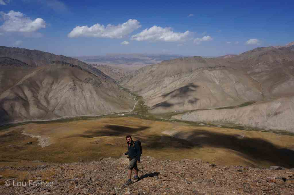 A man hiking amongst arid mountains. Hiking is on of the best things to when backpacking Kyrgyzstan
