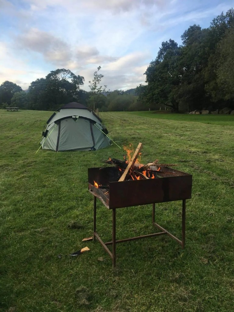 A photo of a fire pit in front of our tent. A good kitchen setup is essential on a car camping checklist