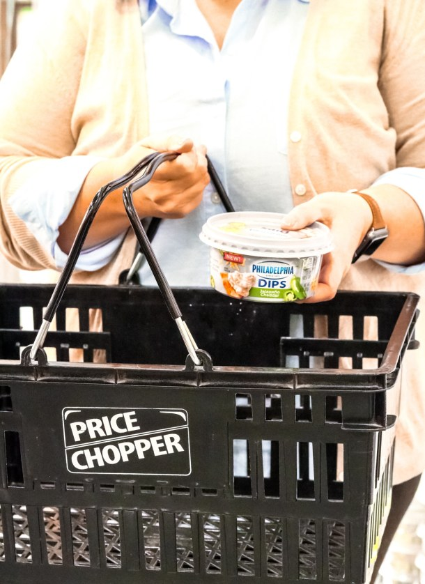 a woman holding a container of KRAFT Philadelphia dip placing it into a Price Chopper basket