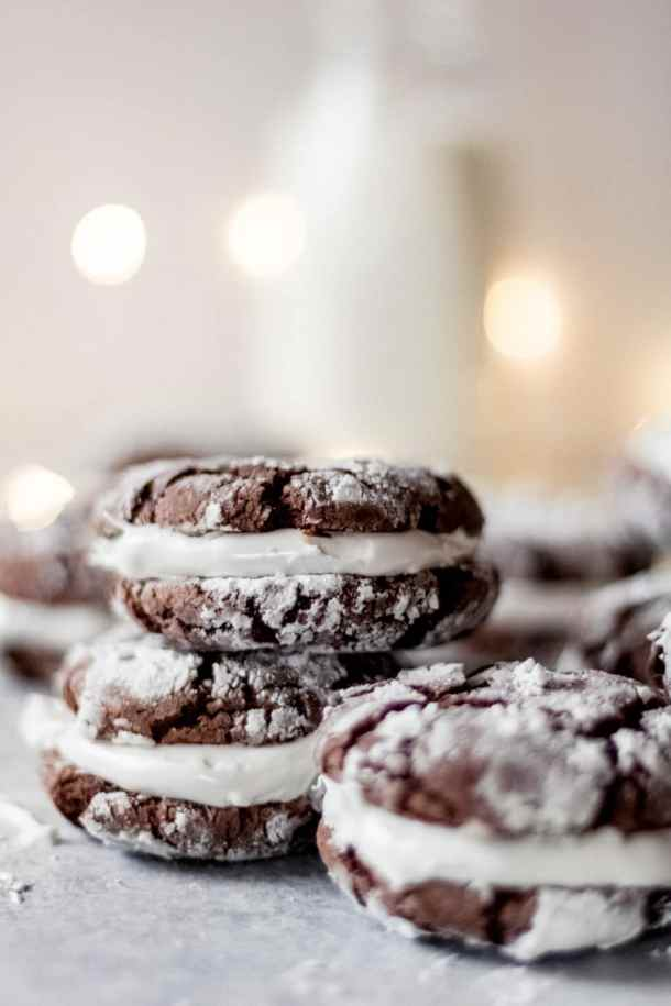 Three hot cocoa sandwich cookies stacked with additional cookies in the background. There's white christmas lights and a jug of milk in the background as well.