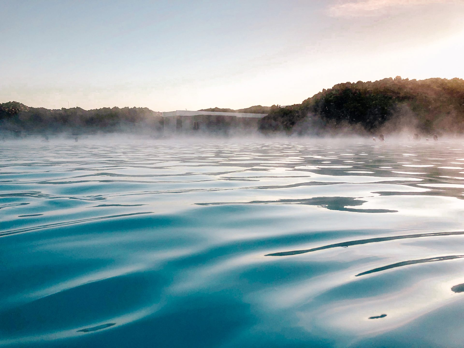 Milky blue water of the blue lagoon located in Iceland. Steam rising up from the water as the sun sets over the horizon.