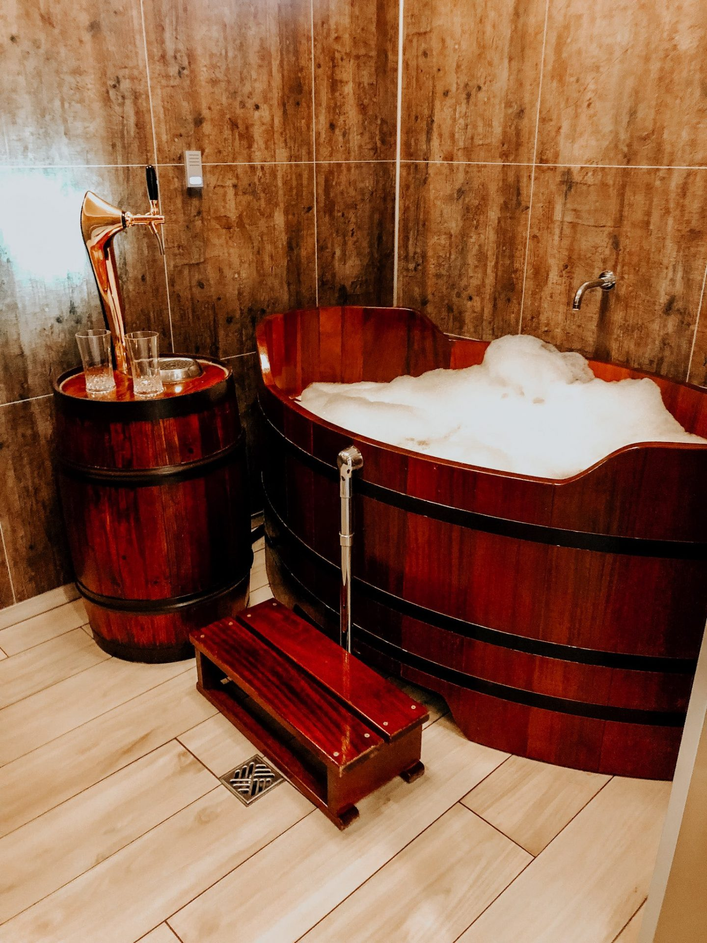 European Beer Travel, wooden bath tub filled with suds and beer with a stepstool into the rub and a one spout draft to drink beer with two beer glasses sitting next to it in a private room.