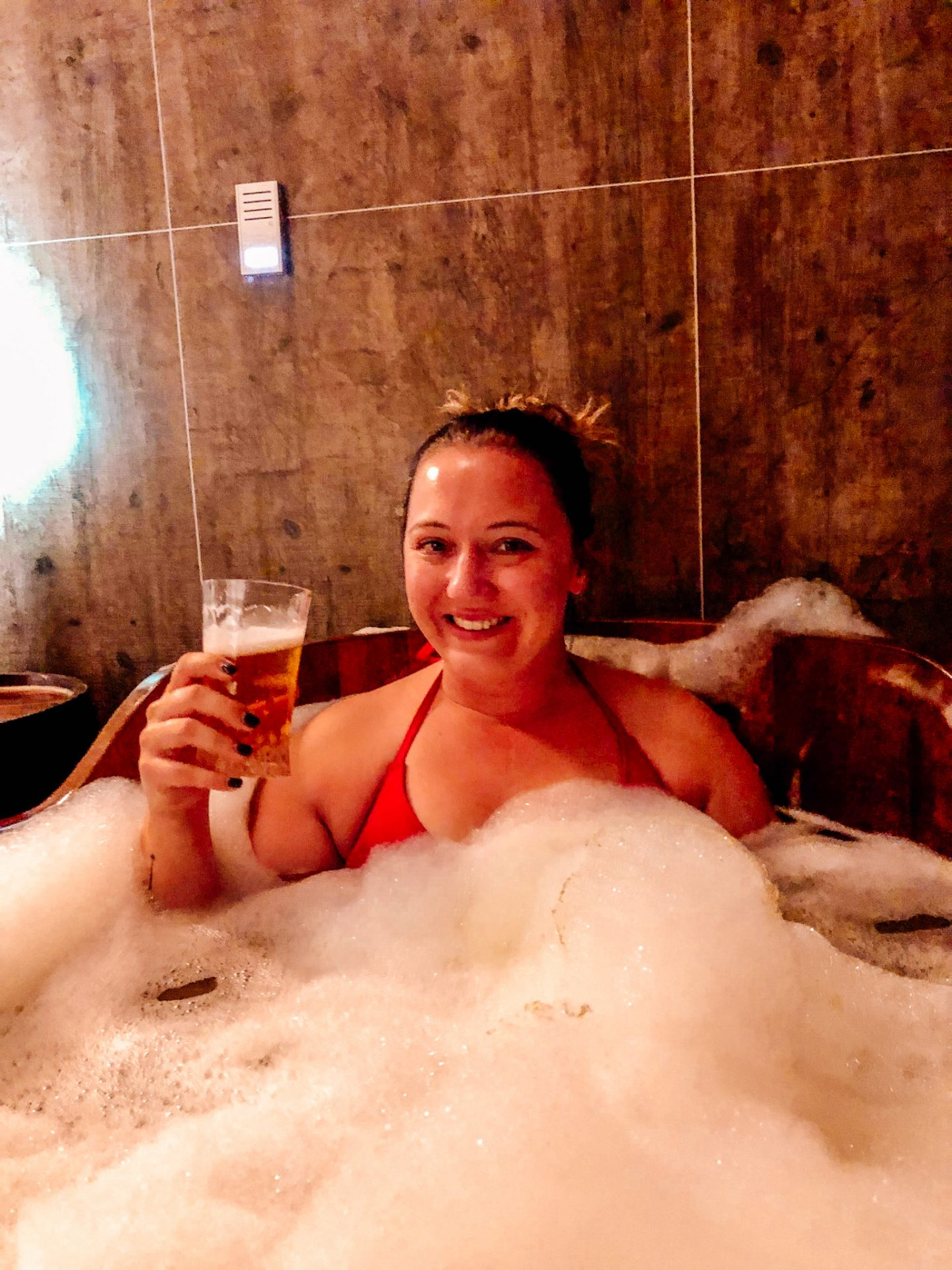 Woman sitting in beer bath with suds, wearing a red bikini holding a glass of beer and smiling.