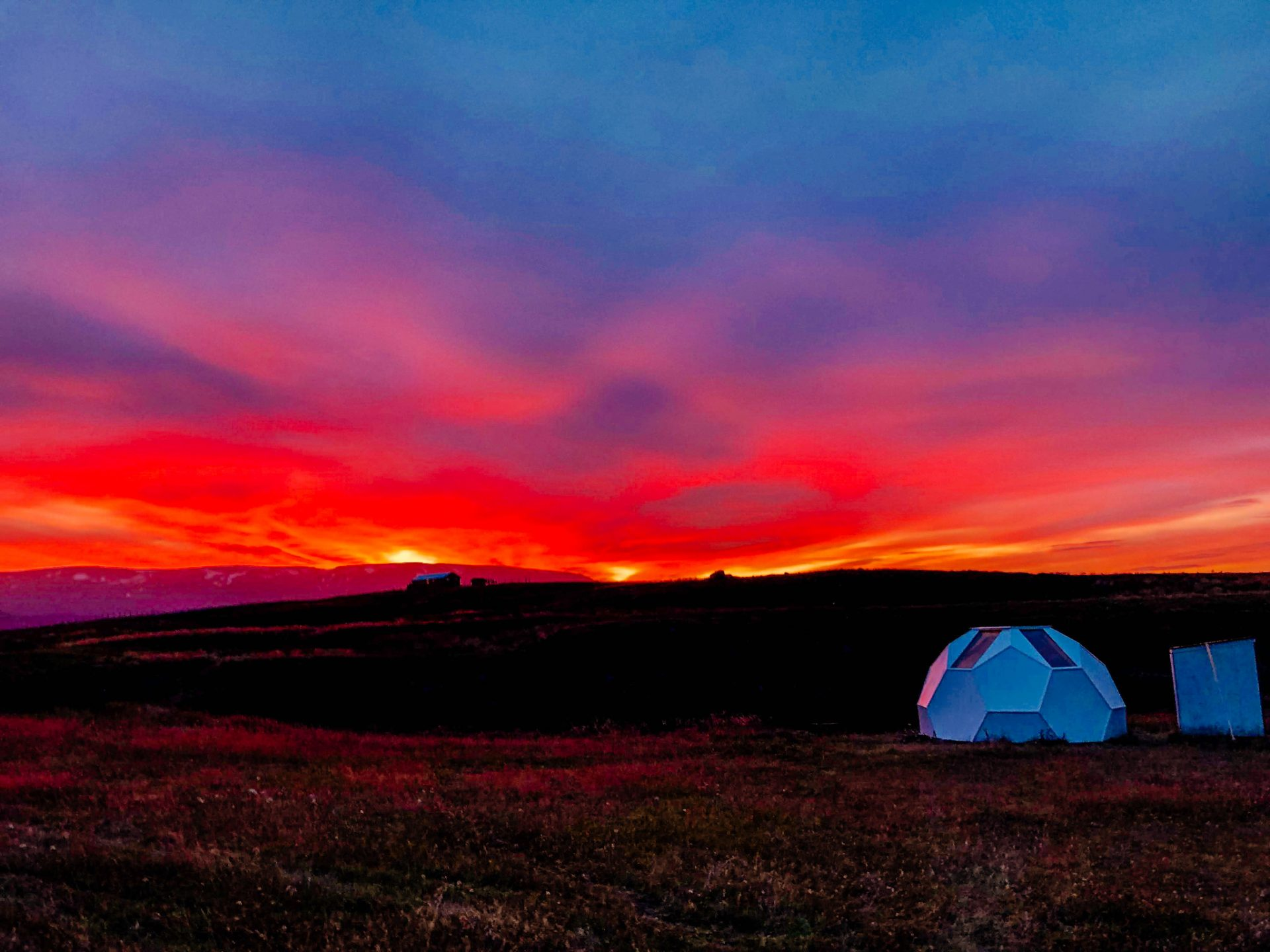 A pink and purple sunrise fire sky overlooking a small white igloo camping structure. Top Experience to have while in Iceland.
