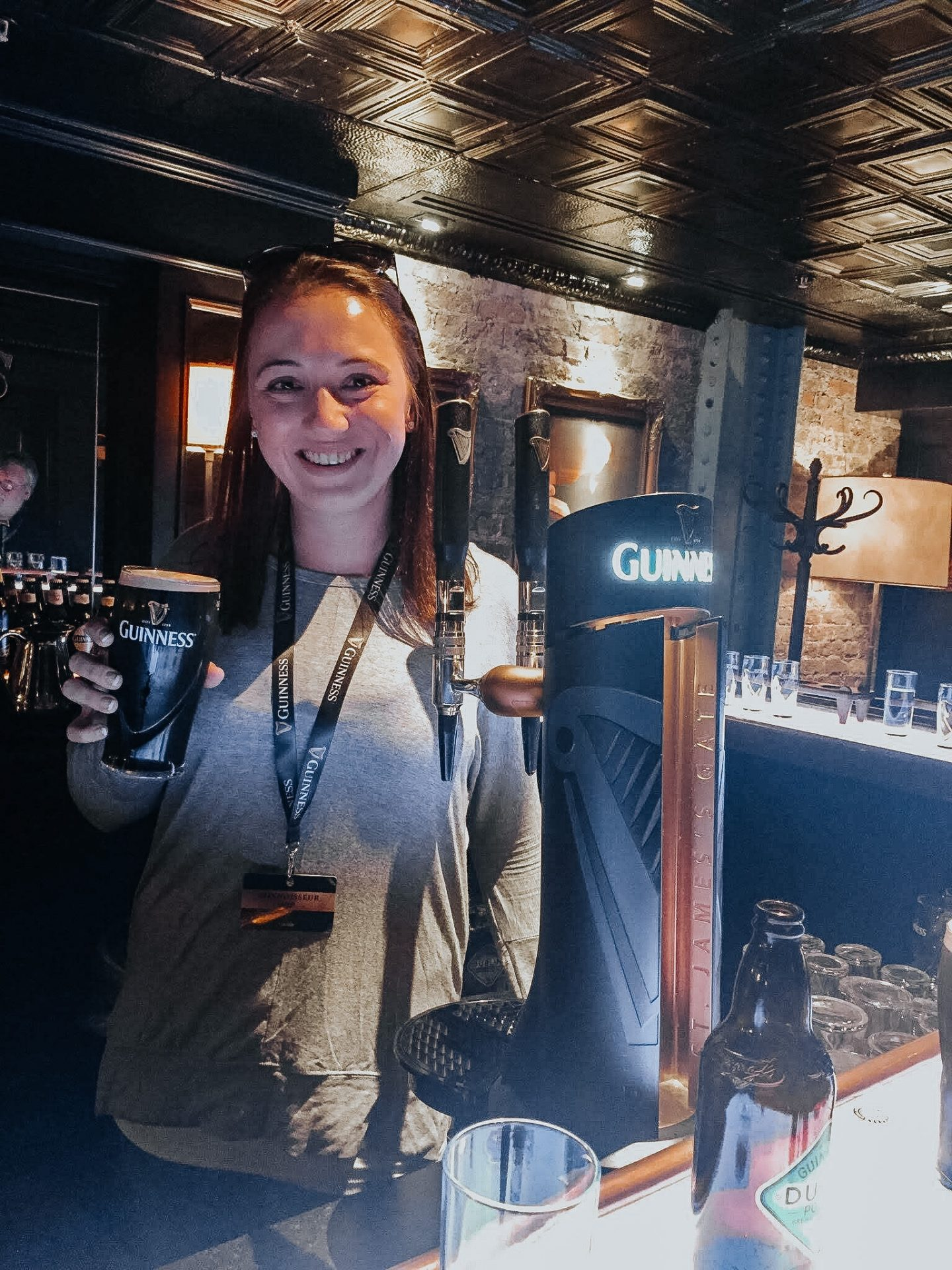 Woman standing in a beer bar in Dublin Ireland Europe holding a full pint of Guinness beer she just poured from the tap next to her holding it up smiling.