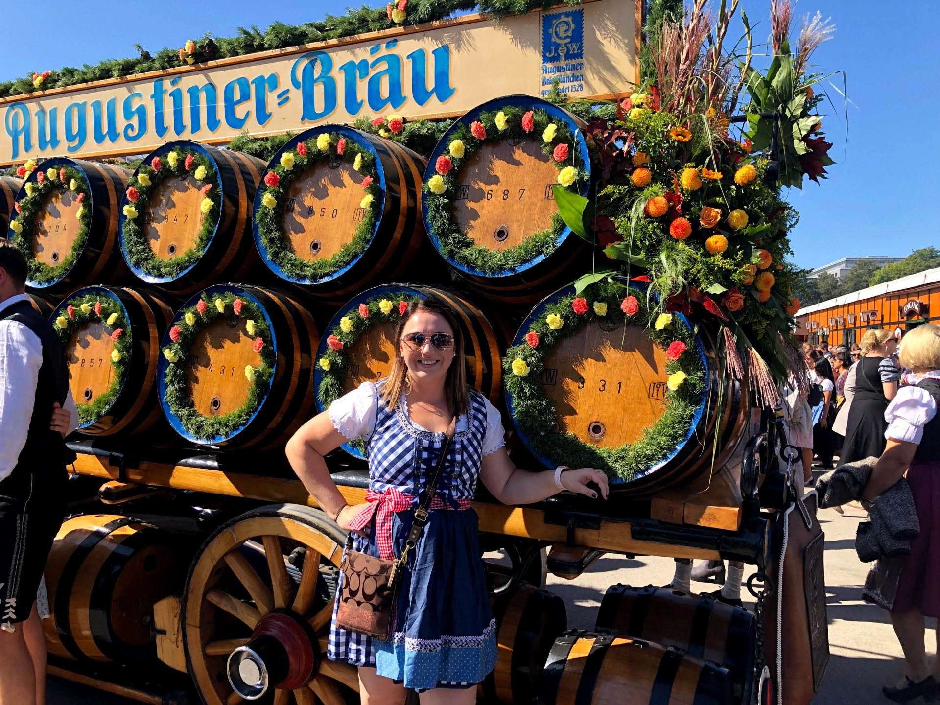 Woman wearing blue and red dirndl standing in front of a float from the Oktoberfest parade in Munich Germany.