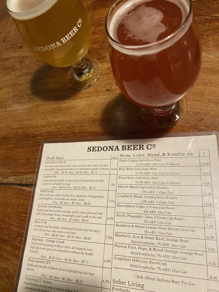 Natural wood table with two glasses of beer on it with a menu state Sedona Beer Co. and listing all of the beers available to order.