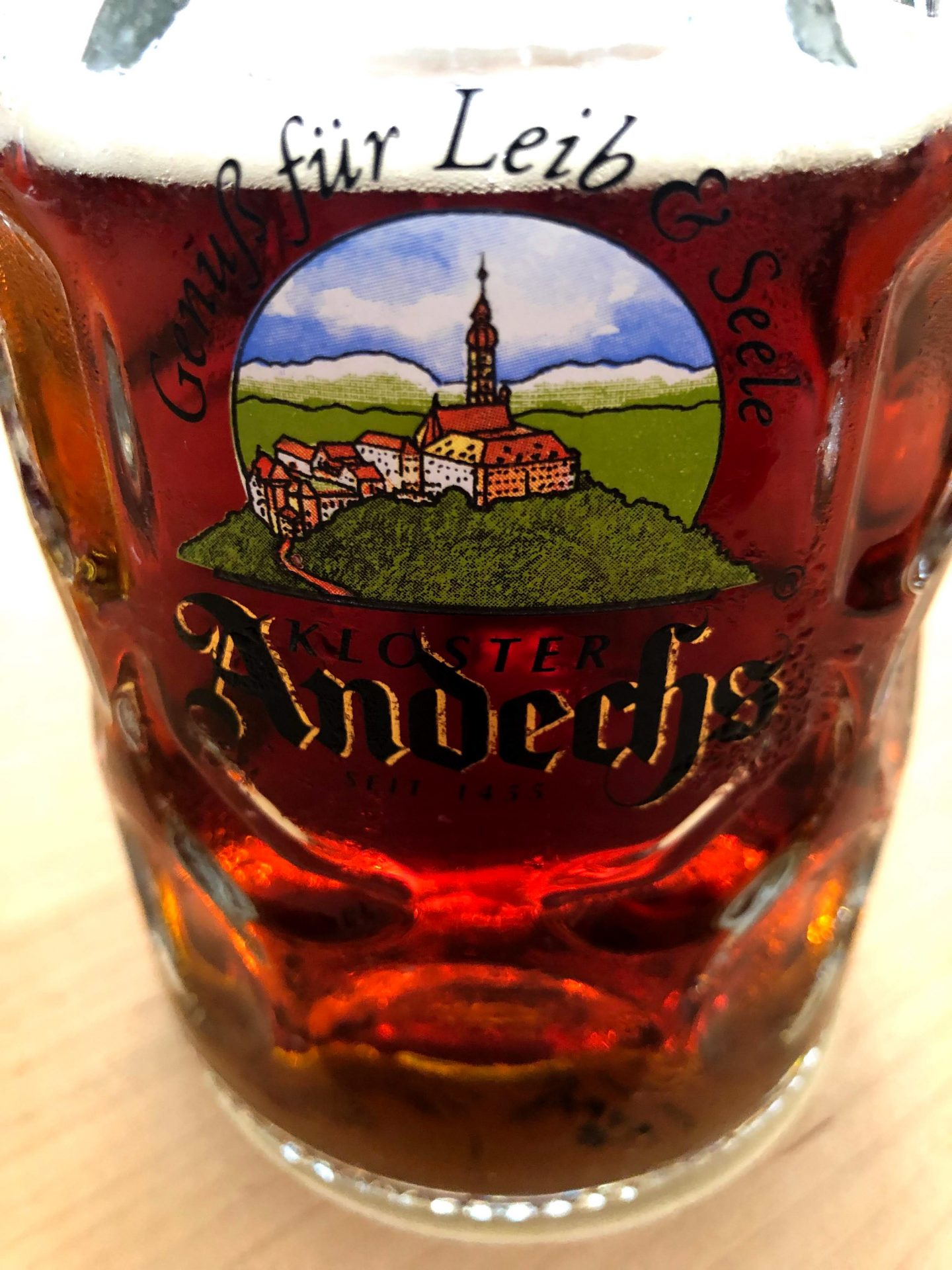 Close up of a glass mug of amber colored beer with the logo Andechs showing