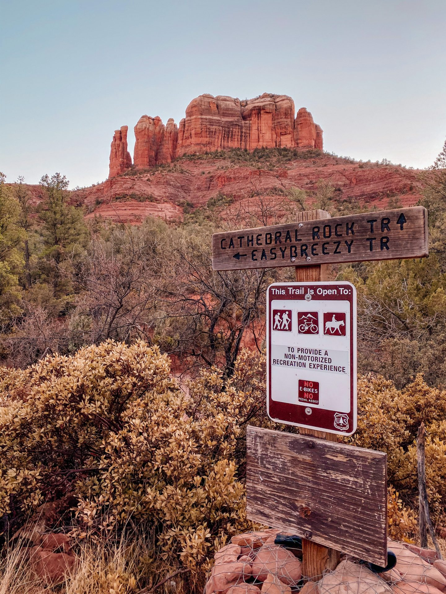 View of the hiking trailhead signs stating Cathedral Rock. Cathedral Rock red rock formation in the background.