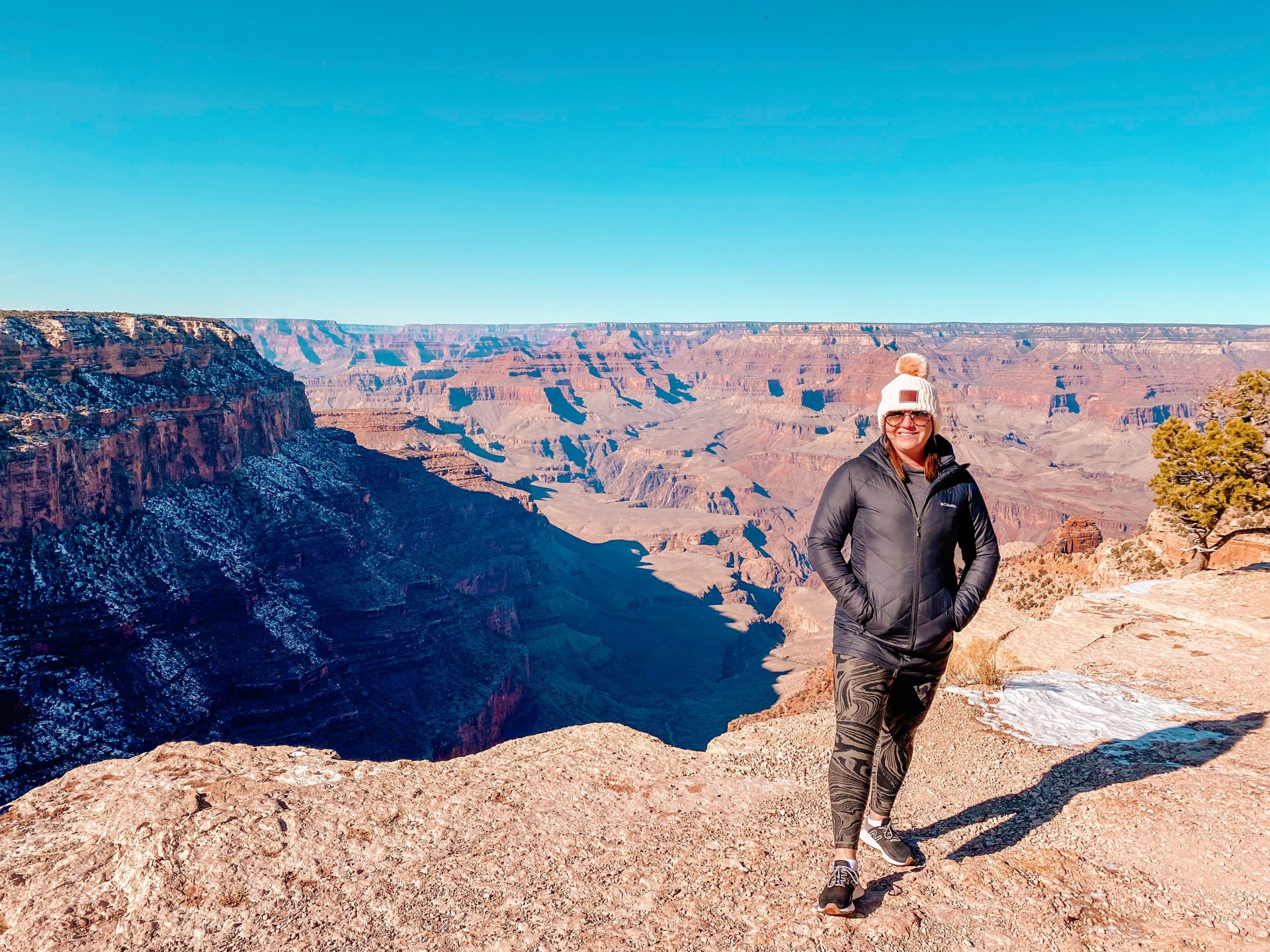 Woman standing smiling at the camera with hands in pocket with the backdrop of the Grand Canyon in Arizona.