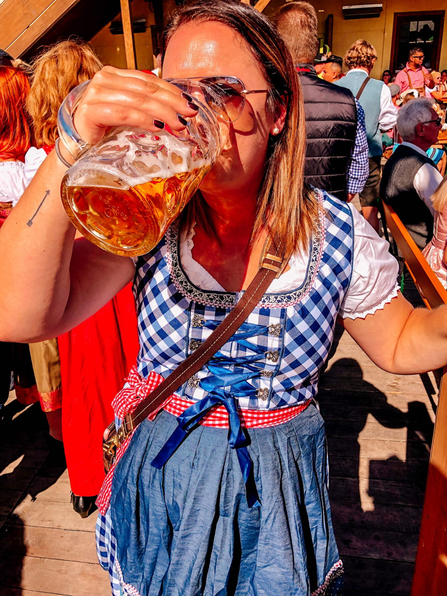 Woman wearing a red and blue dirndl and sunglasses drink out of a 1L glass mug of beer at Oktoberfest in Munich Germany Europe.