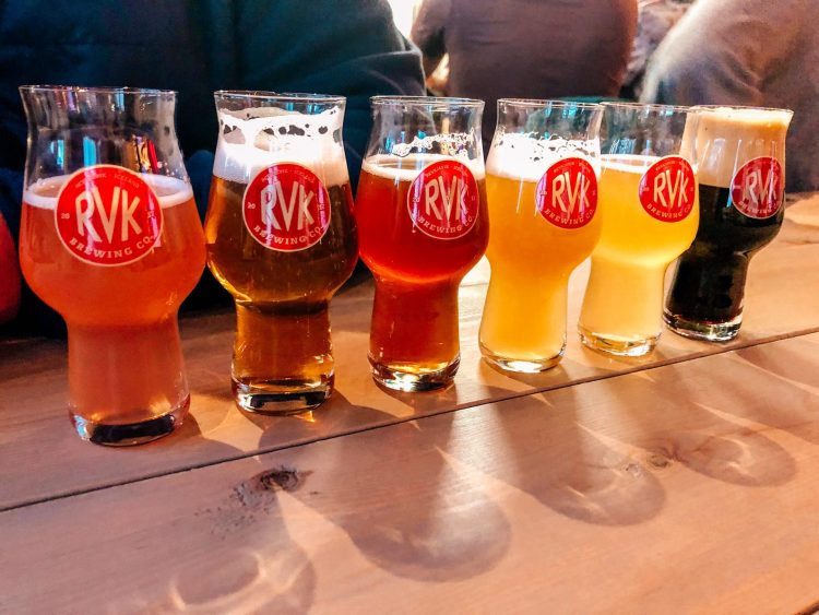 RVK brewing located in Reykjavik Iceland. Flight of different colored beers from golden to amber to dark brown sitting alongside each other on a natural colored table top.