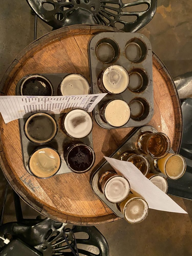 multiple muffin tins holding beer tasting glasses sitting a top a round wooden table at new heights brewing.