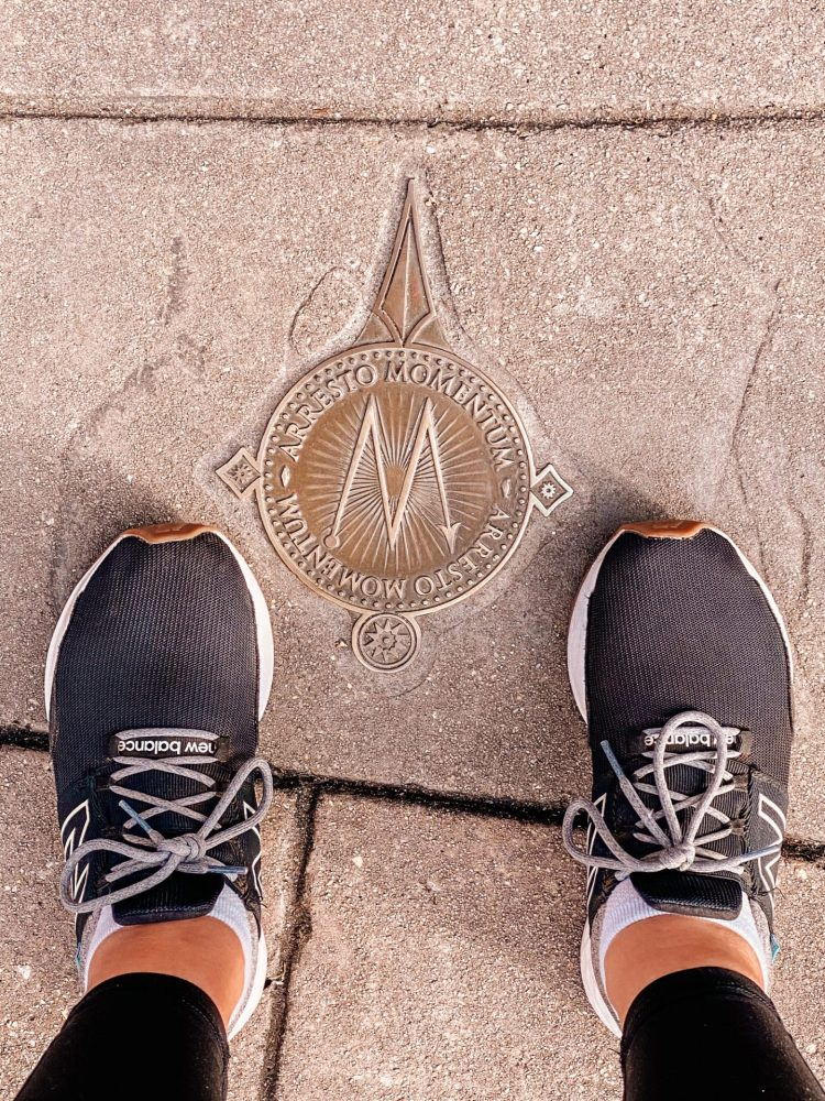 Ground bronze magic marker with feet around it at the Wizarding World of Harry Potter Universal Studios Florida