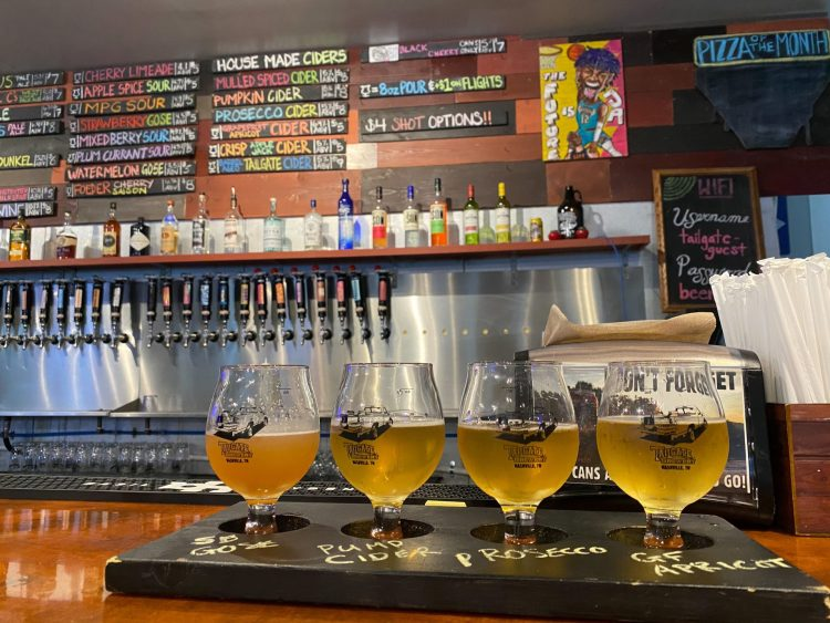 Flight of golden beers sitting atop a bar with the beer taps on the back wall and list of tap beers in the background.