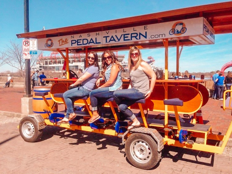 Three girls sitting on the bike seats of the Nashville Pedal Tavern. Things to do in Nashville. Girls smiling at the camera prior to the Nashville pedal Tavern bike tour.