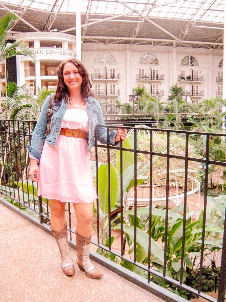Woman standing in the Opryland hotel wearing a pink dress with cowboy boots and a jean jacket.