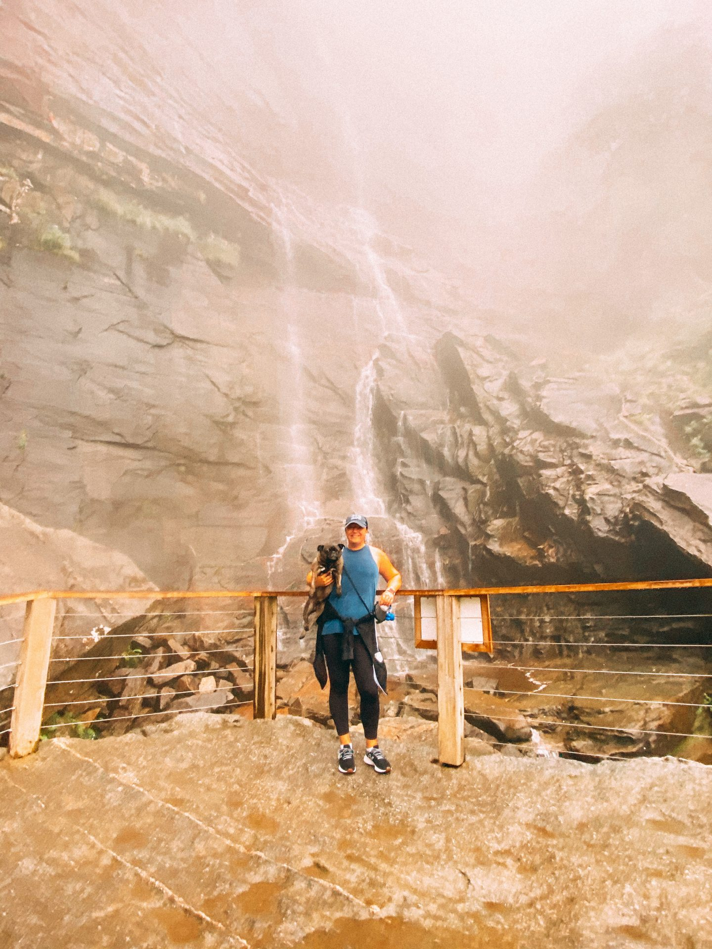 Woman holding a dog with a waterfall behind them while hiking at chimney rock state park in north carolina