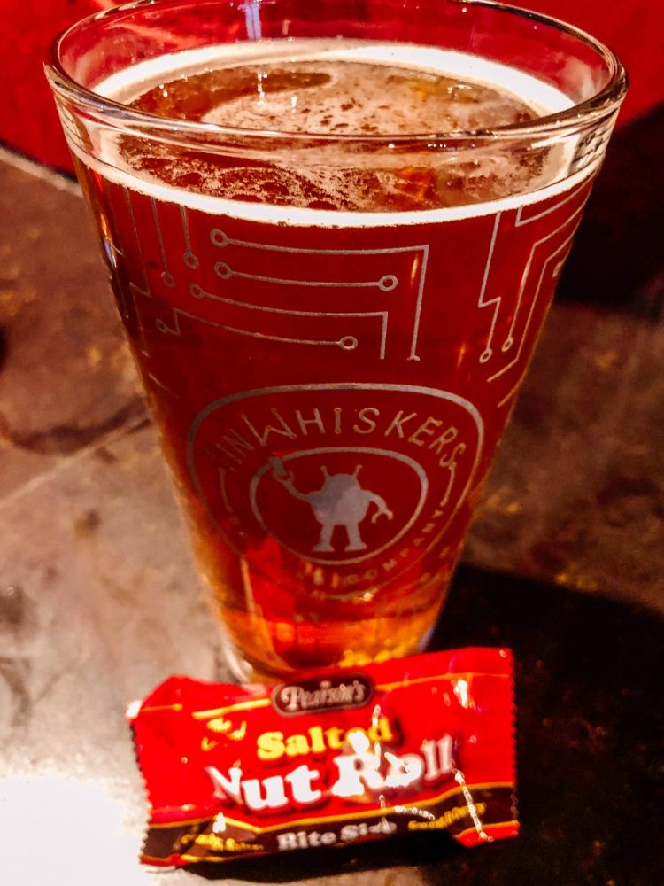 pint glass of beer with the Tin Whiskers logo on it and a mini size candy bar of a salted nut roll in St. Paul Minnesota during a brewery crawl