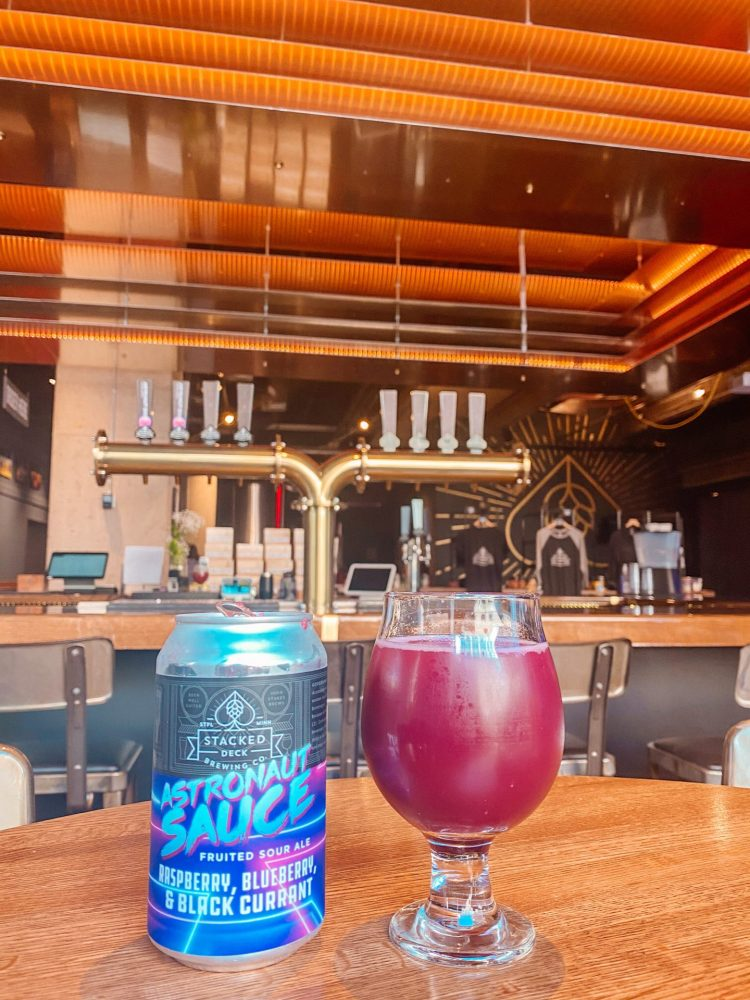 a glass and can of astronaut sauce fruited sour beer at stacked deck brewing in st. paul minnesota