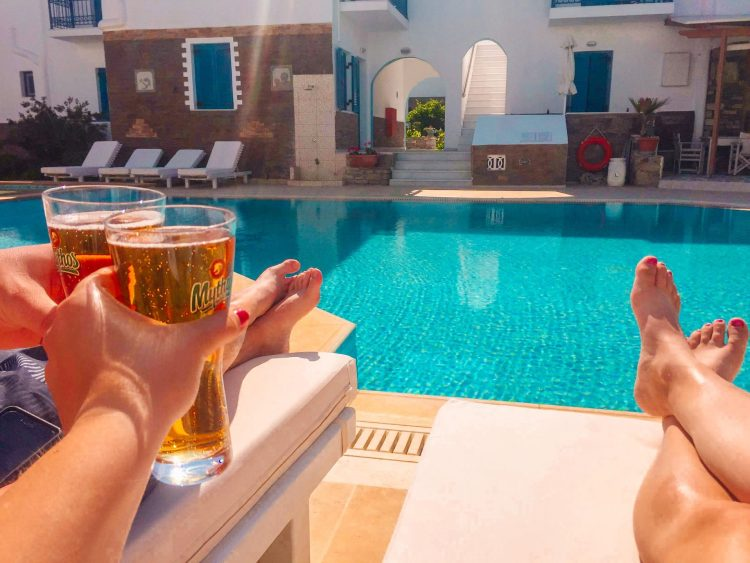 Agios Prokopios hotel by the pool with a Mythos beer cheersing on Naxos island a place to visit in Greece