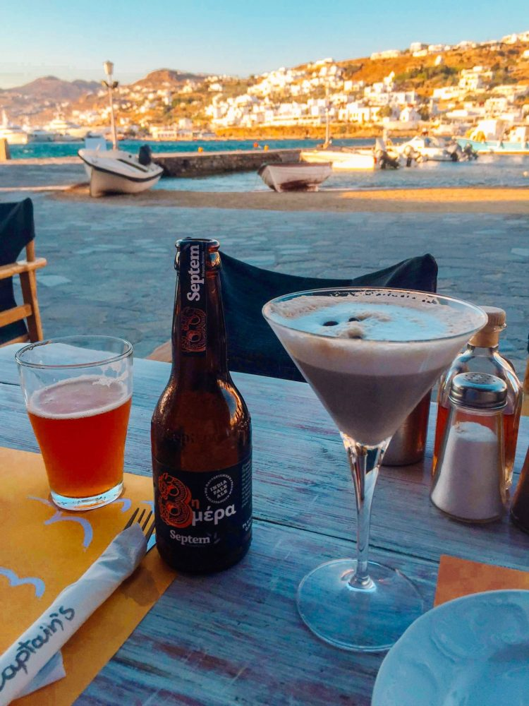 Craft beer and an espresso martini sitting on a table dining at Captains al fresco in Mykonos Greece