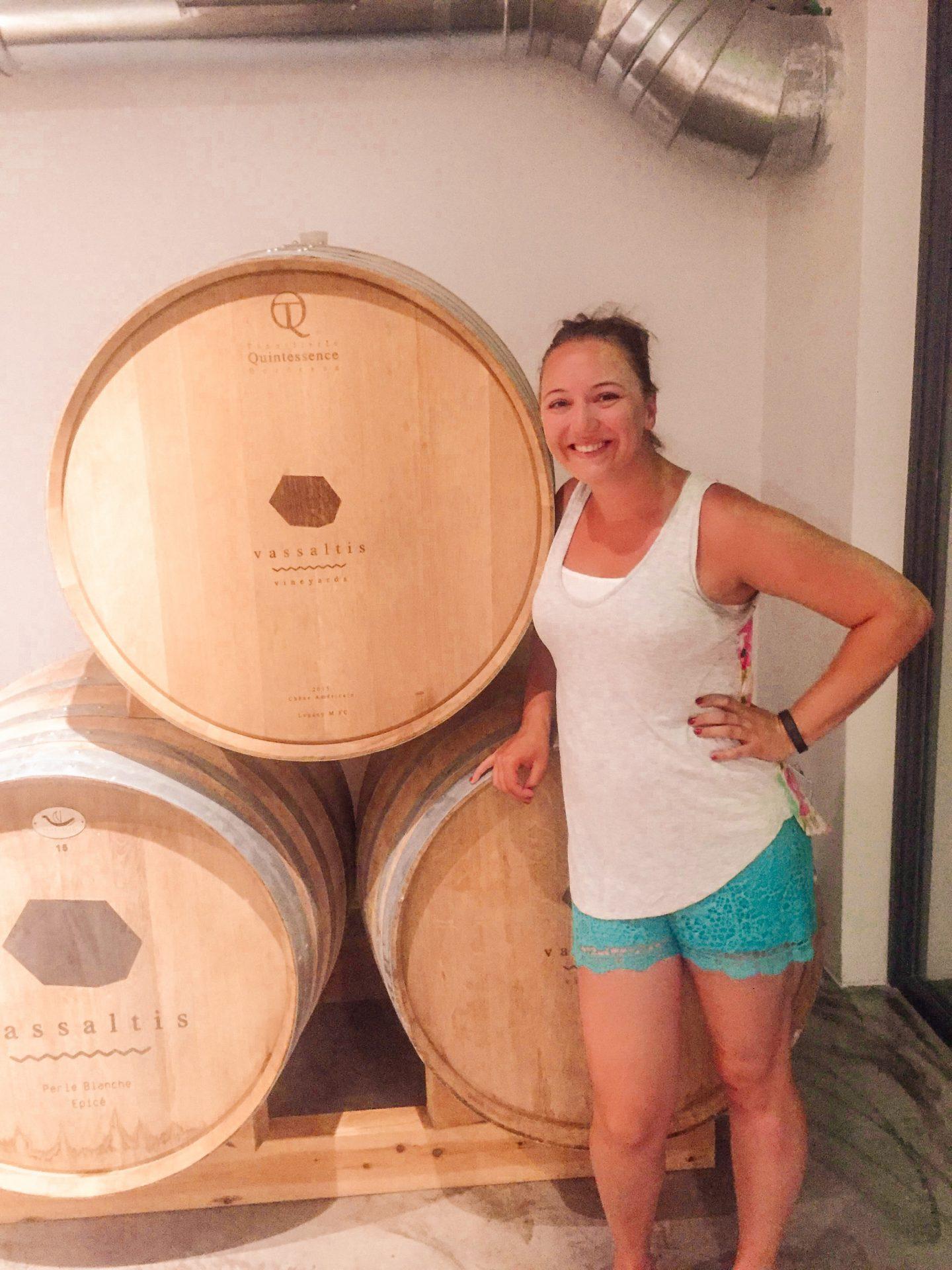 woman standing by wine barrels at vassaltis winery on Santorini Greece