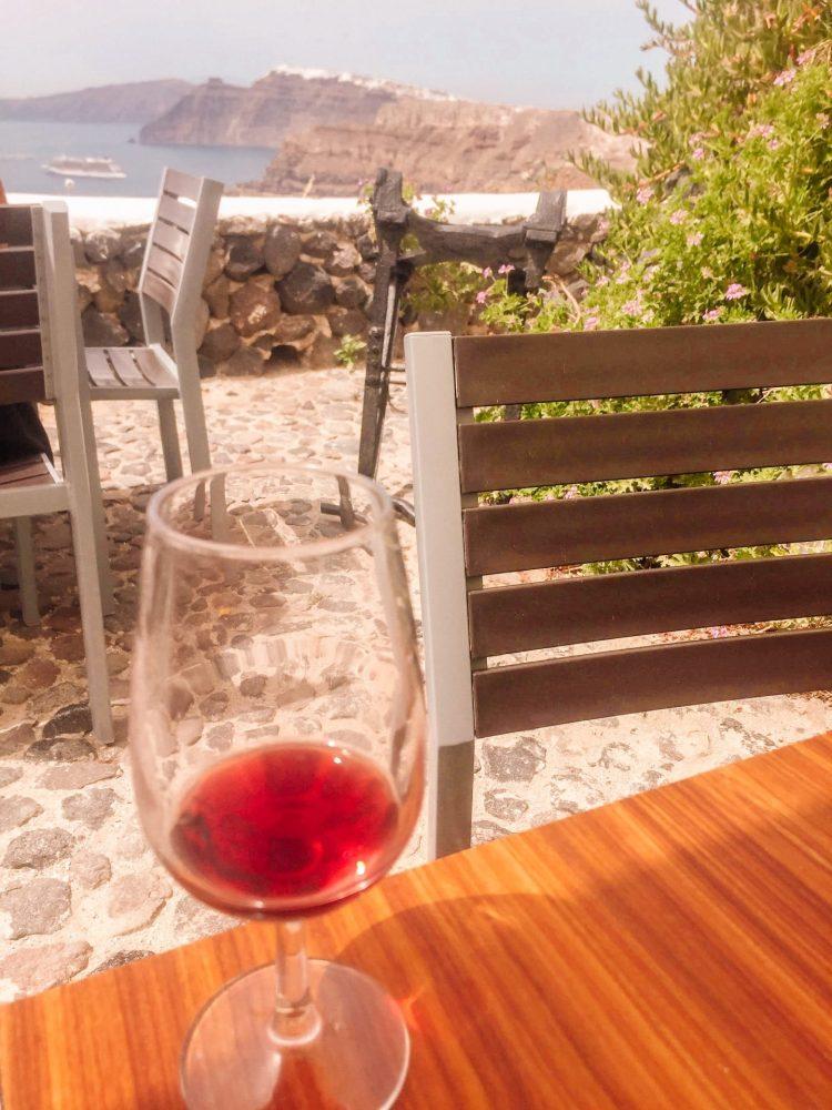 glass of wine with an amazing caldera view on Santorini Greece