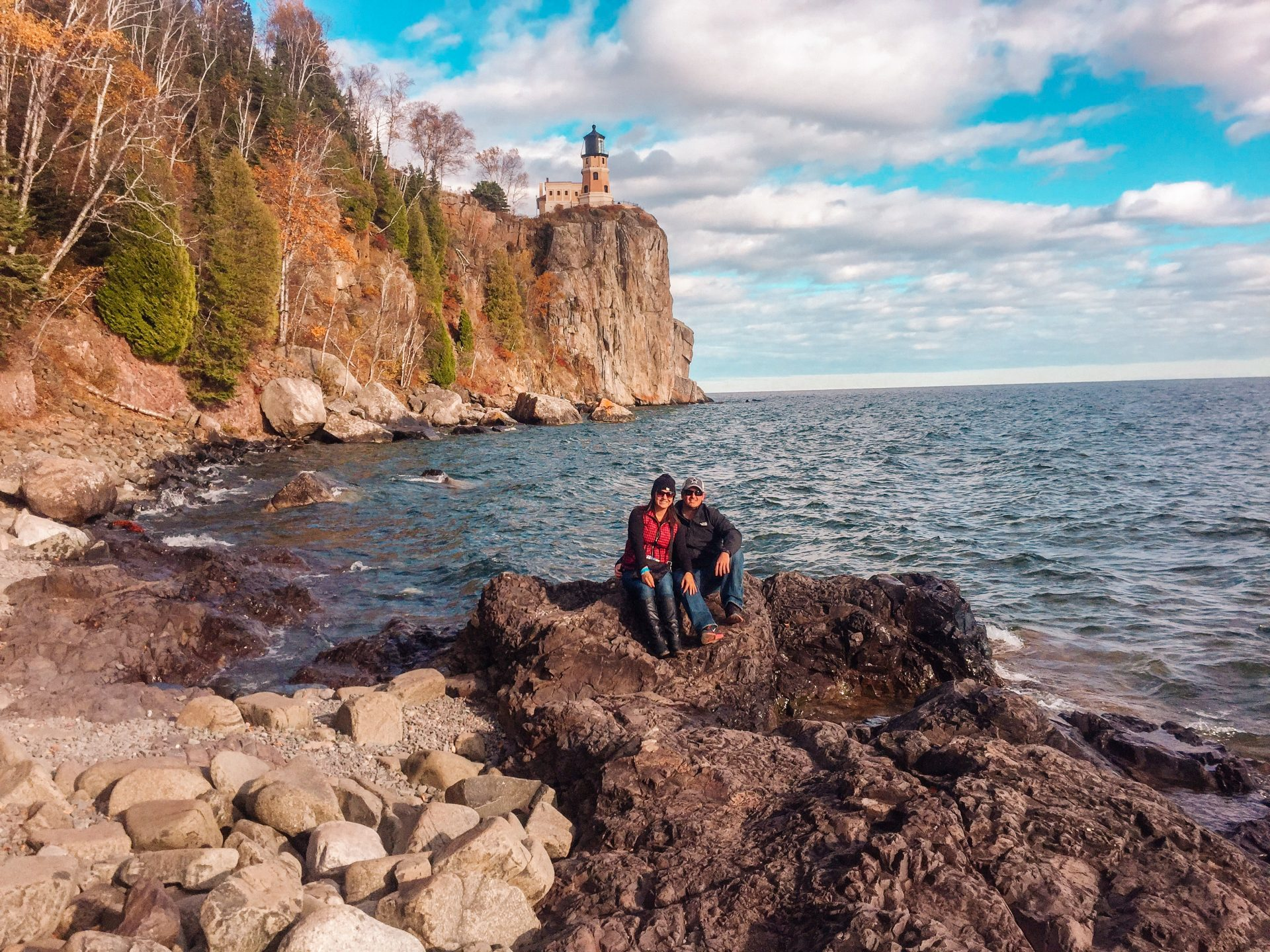 woman and man sitting on Rugged Shore line along Lake Superior from Split Rock Lighthouse State Park