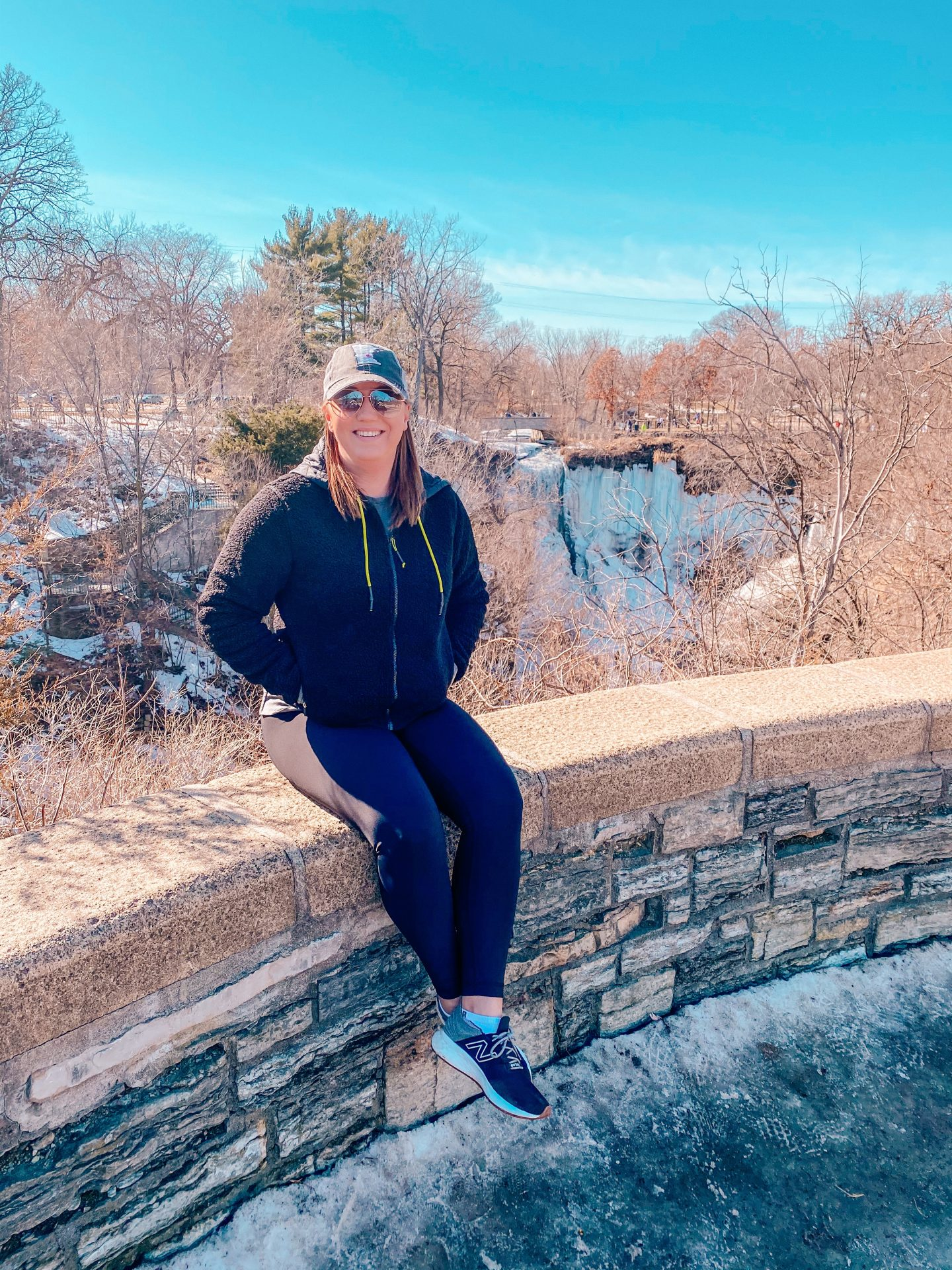 Woman sitting on brick ledge over looking the frozen minnehaha falls waterfall in minneapolis minnesota in the spring