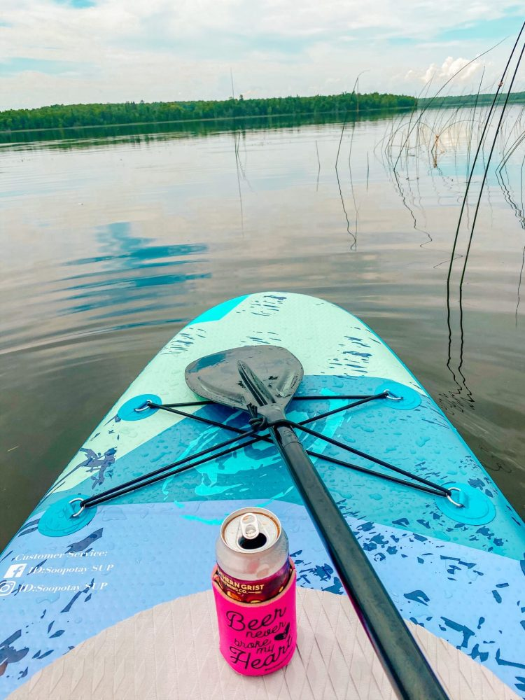 colorful paddle board with a paddle on it and an open beer in a coozie on a calm Minnesota lake in the summer