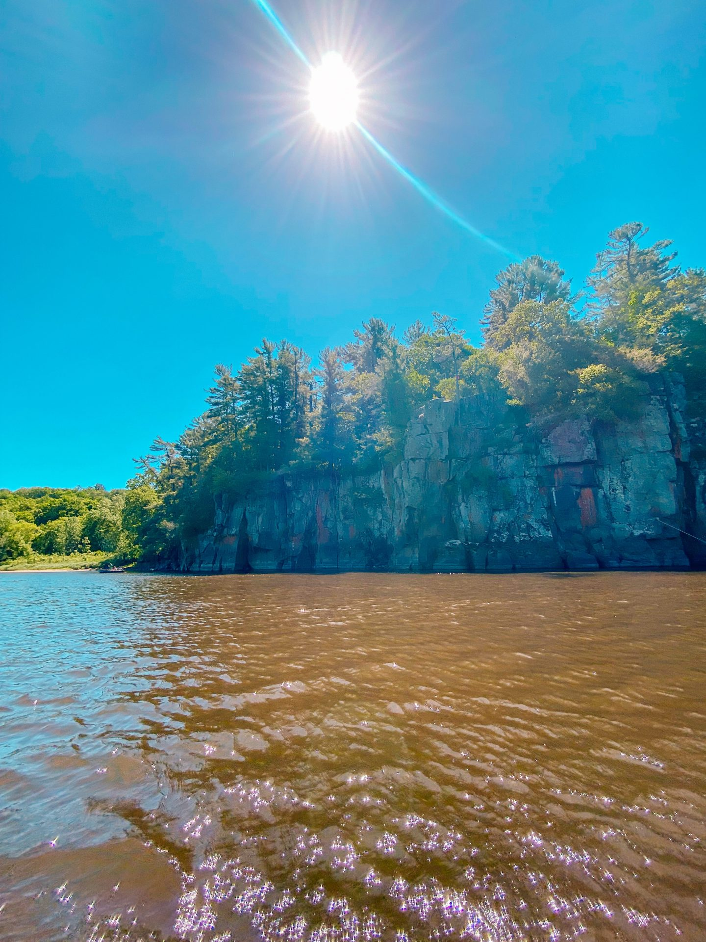 the gorgeous rocky bluffs and green trees along the st croix river in Minnesota during the summer