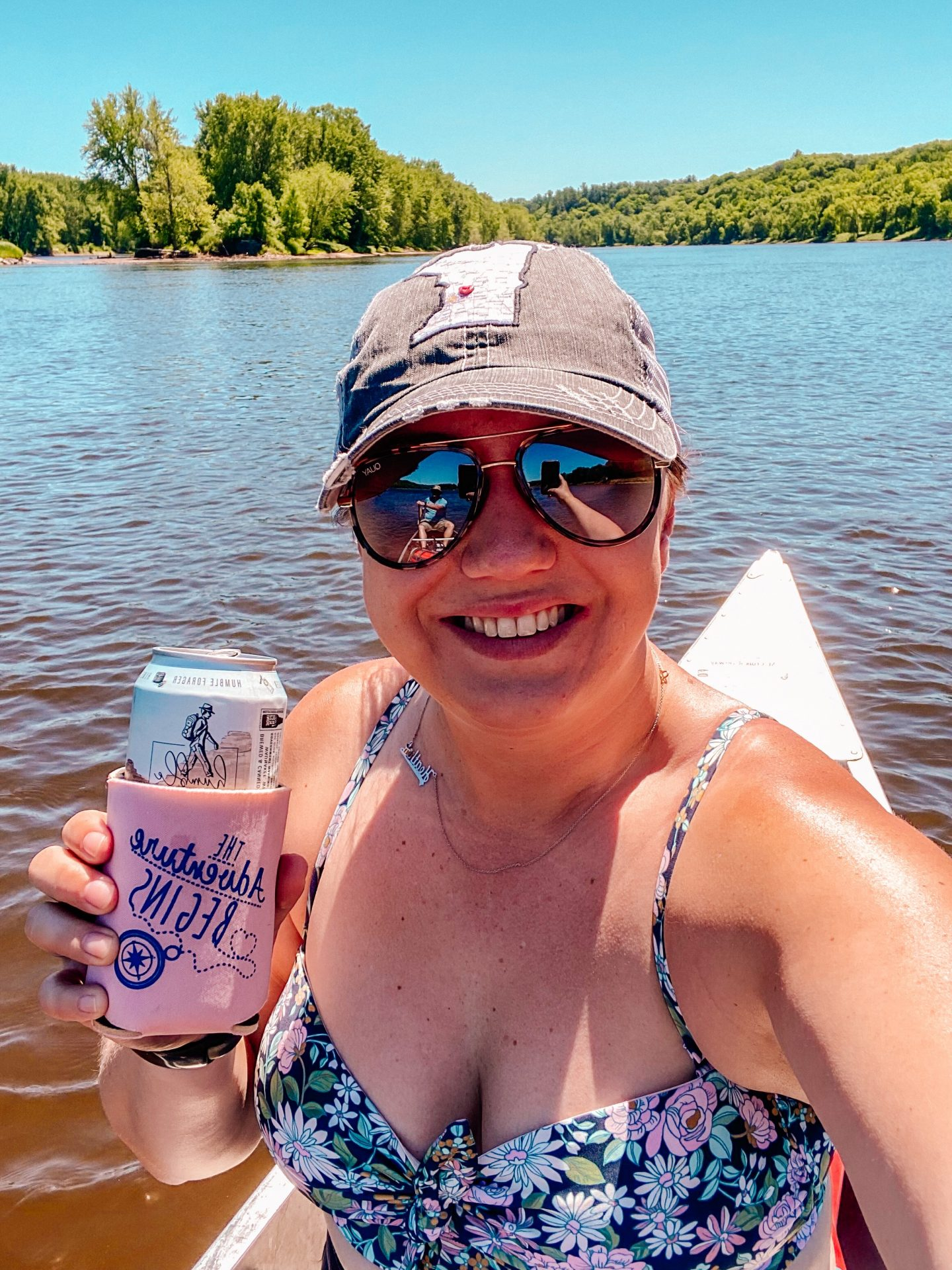 woman smiling with a baseball hat, sunglasses and a bikini on in a canoe while holding up a beer